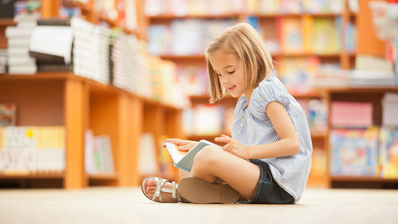 Girl sitting on floor of library with book